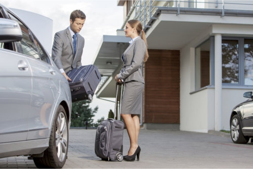 businesspeople unloading luggage from car